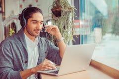 Человек усмехаясь используя ноутбук дома в живущей комнате стоковая фотография rf