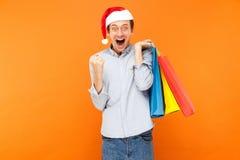 Человек успеха счастья держа пакеты, показывая знак победы и Стоковое Фото