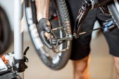 Человек устанавливая новые педали на велосипед стоковое изображение rf
