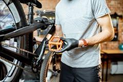 Человек устанавливая новые педали на велосипед стоковое фото rf