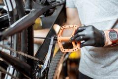 Человек устанавливая новые педали на велосипед стоковая фотография rf