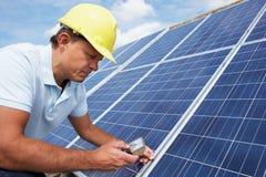 Человек устанавливая панели солнечных батарей стоковая фотография