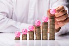 Человек устанавливая Piggybank на увеличении штабелированных монеток стоковые фото