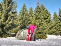 Человек установил snowshoes и trekking ручки для прогулки Светлый шатер установленный в горы Отключение зимы стоковая фотография rf