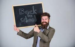 Человек учителя бородатый стоит и держит классн классный с надписью назад к предпосылке серого цвета школы Учитель рекламирует на стоковые изображения rf