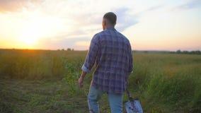 Человек фермера идя через поле на заходе солнца или восходе солнца Снесите саженец дерева и лопаткоулавливатель, концепцию - рабо акции видеоматериалы
