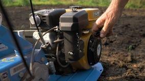 Человек фермер в пригородном районе, огород, плужки земля с рыхлителем, ручным плужком мотора видеоматериал