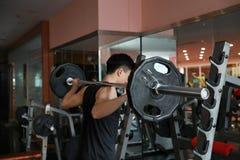 Человек фитнеса в спортзале делая сидение на корточках Человек с гимнастикой тренажера веса гантели Крытый, инструктор Стоковые Фотографии RF