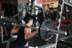 Человек фитнеса в спортзале делая сидение на корточках Человек с гимнастикой тренажера веса гантели Крытый, инструктор Стоковое фото RF