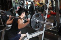 Человек фитнеса в спортзале делая сидение на корточках Человек с гимнастикой тренажера веса гантели Крытый, инструктор Стоковые Изображения