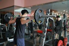 Человек фитнеса в спортзале делая сидение на корточках Человек с гимнастикой тренажера веса гантели Крытый, инструктор Стоковое Изображение