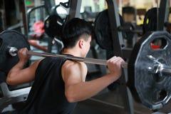 Человек фитнеса в спортзале делая сидение на корточках Человек с гимнастикой тренажера веса гантели Крытый, инструктор Стоковое Фото