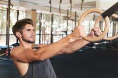 Человек фитнеса льнет к кольцу стоковое изображение rf