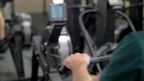 Человек фитнеса молодой используя грести машину в спортзале видеоматериал