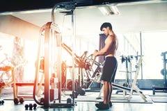 Человек фитнеса сильный делая тяжеловесную тренировку на машине в спортзале Стоковые Фото