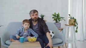 Человек футбольных болельщиков бородатый и его маленький ребенок смотрят спичку на ТВ дома, цели celebratong и едят хрустящие кор сток-видео