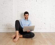Человек хипстера молодой на ноутбуке в его новой пустой квартире ища в Интернете покупая мебель стоковые фото