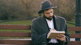Человек художника Hipser творческий в чертеже шляпы и пальто с ручкой и sketchbook сидя на улице города bench на парке Стоковые Изображения RF
