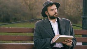Человек художника Hipser творческий в чертеже шляпы и пальто с ручкой и sketchbook сидя на улице города bench на парке Стоковое Изображение RF