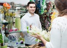 Человек цветков продавца женщины предлагая Стоковые Изображения