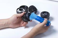 Человек чистит удалять щеткой объектив объектива с щеткой Рядом на таблице другие винтажные объективы стоковые фотографии rf