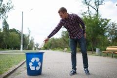 Человек чистки пустой пластичной выпивая бутылки вышел на пол дороги Концепция охраны окружающей среды Стоковое Изображение RF