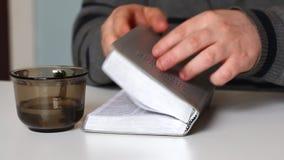 Человек читает библию, делает закладку, и закрывает книгу видеоматериал