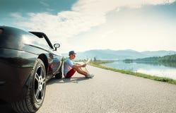 Человек читает дорожную карту сидя около его cabriolet Стоковое Изображение RF