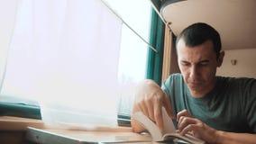 Человек читая книгу в путешествии поезда длинном поездка на поезде тренера образа жизни концепции перемещения железной дороги взг сток-видео