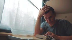 Человек читая книгу в путешествии поезда длинном E взгляд красивый из окна видеоматериал