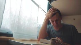 Человек читая книгу в путешествии поезда длинном E взгляд красивый из окна акции видеоматериалы