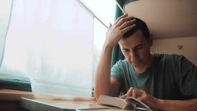 Человек читая книгу в путешествии поезда длинном E взгляд красивый из окна сток-видео