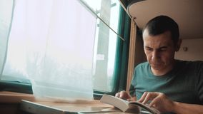 Человек читая книгу в путешествии поезда длинном E образ жизни взгляда красивый от видеоматериал