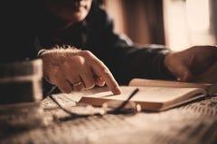 Рука книги чтения старшего человека в доме престарелых стоковые фотографии rf