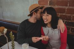Человек шепча в ухе женщины на кафе Стоковые Изображения RF