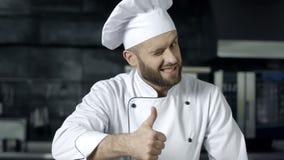 Человек шеф-повара представляя на профессиональной кухне Профессиональный шеф-повар с большими пальцами руки вверх акции видеоматериалы