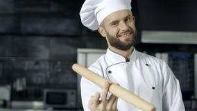 Человек шеф-повара представляя с роликом на кухне Усмехаясь шеф-повар играя со штырем ролика сток-видео