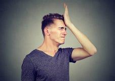 Человек шлепая руку на голове имея сожаления стоковые фотографии rf