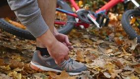 Человек Active подходящий связывая ботинок в парке движение медленное видеоматериал
