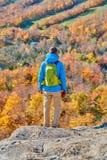 Человек Backpacker на блефе художника в осени стоковые фото