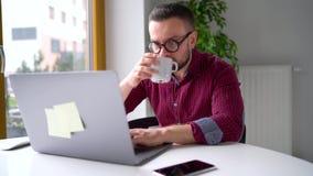 Человек Beared в стеклах сидя дома офис и работая на ноутбуке