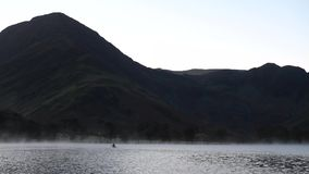 Человек Canoeing в озере Buttermere перед восходом солнца видеоматериал