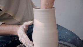 Человек Ceramist держа глину в руках и делая новую вазу в stu видеоматериал