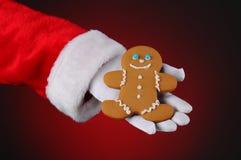 Человек Gingerbread удерживания Santa Claus в его руке Стоковые Изображения RF