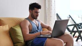 Человек Handosme работая дома на столе компьютера акции видеоматериалы