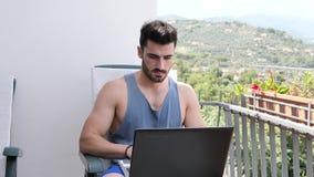 Человек Handosme работая дома на столе компьютера видеоматериал