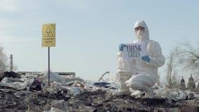 Человек Hazmat в защитные шоу костюма подписывает думает зеленое на сбросе хлама с Outdoors опасности радиации указателя видеоматериал