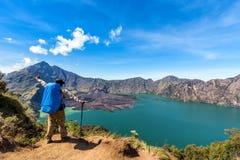Человек Hiker с рукой рюкзака распространяя, наслаждается и счастливый с действующим вулканом Baru Jari, озером Segara Anak и сам Стоковое Изображение