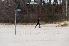 Человек jogging во время сезона зимы на пляже Латвии Jurmala стоковое фото rf