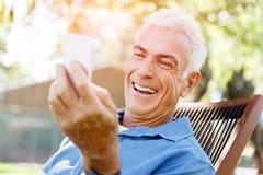 Человек LoMature outdoors используя мобильный телефон стоковые фотографии rf